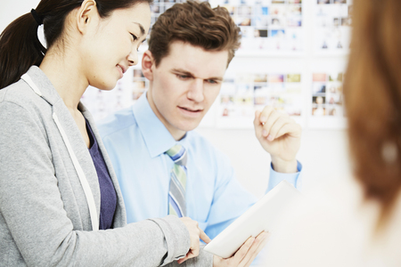 Business colleagues in discussion with digital tablet