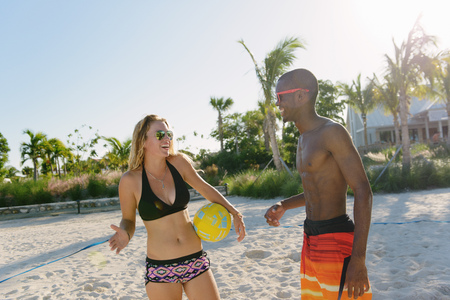 Two young adult friends with beach volleyball, Providenciales, Turks and Caicos Islands, Caribbean