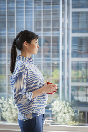 ponderous: Portrait of young businesswoman looking out of window
