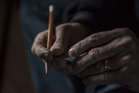 check out: Close up of male hands holding a pencil and piece of wood