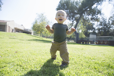 shadowed: Baby boy learning to walk on grass