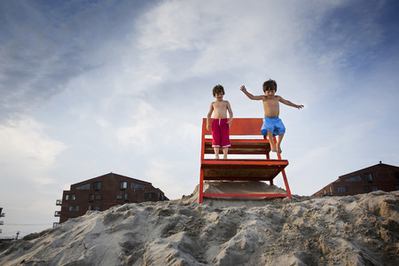 Two boys jumping off red notice board, Long Beach, New York State, USA LANG_EVOIMAGES