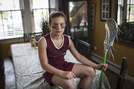 enraged: Girl wearing lacrosse uniform, sitting on dining table