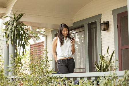 Young woman using smart phone on porch LANG_EVOIMAGES