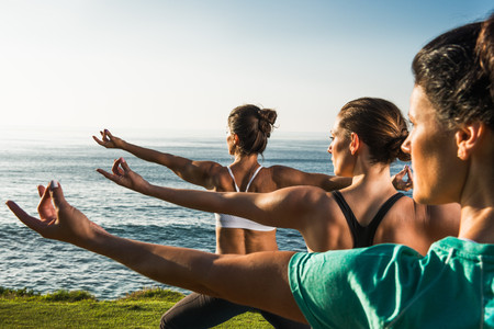 Women on cliff, practising yoga LANG_EVOIMAGES