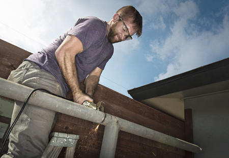home decorating: Builder on ladder sawing metal piping