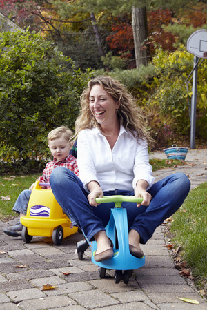 3 4 years: Mother and young son riding on toy cars in garden