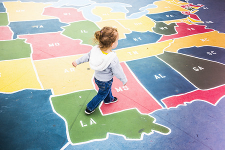 sweatshirts: Toddler walking over map of USA in playground
