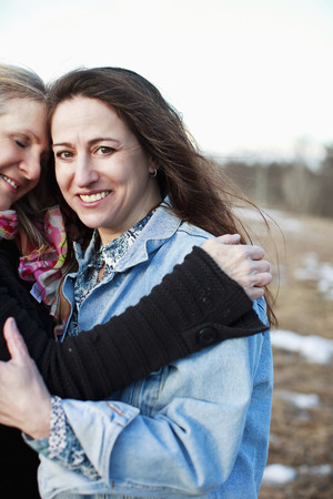 wintry weather: Portrait of mature women hugging outdoors