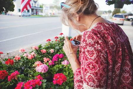 Mature woman photographing flowers LANG_EVOIMAGES