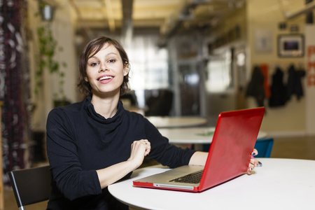 technology: Portrait of female designer with red laptop