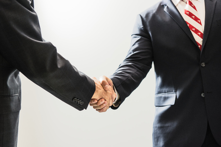 solicitors: Cropped shot of male business lawyers shaking hands in office LANG_EVOIMAGES