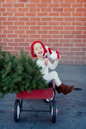chuckle: Girl sitting in trailer with christmas tree