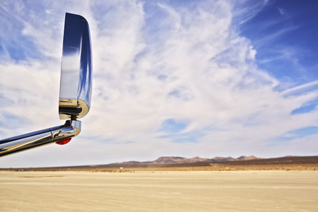 View of car wing mirror and arid landscape LANG_EVOIMAGES