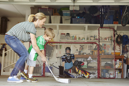 work related: Mother playing hockey in garage with two sons