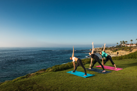 Women on cliff, in yoga position