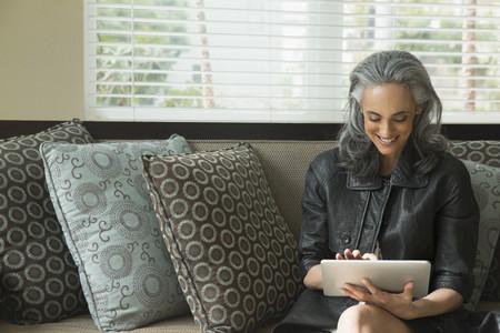 browns: Woman using digital tablet on sofa