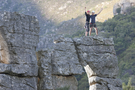 pastoral scenery: Young rock climbing couple celebrating on rock formation