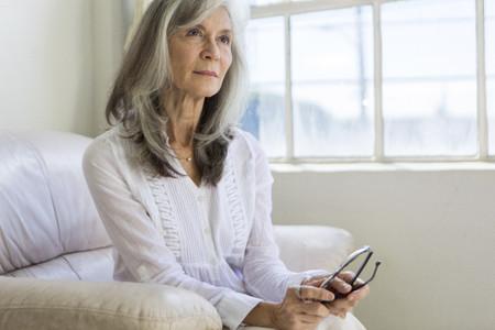 Portrait of attractive senior woman sitting in apartment