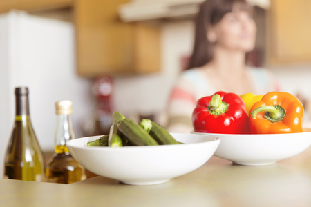 Mid adult woman in kitchen with bowls of vegetables on counter LANG_EVOIMAGES