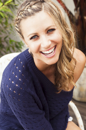 chuckle: Young woman wearing purple sweater laughing