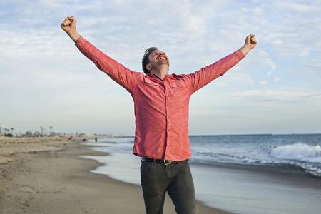 Young man celebrating on beach, Long Beach, California, USA LANG_EVOIMAGES