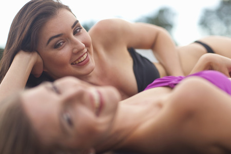 liberating: Two young women on river pier sunbathing LANG_EVOIMAGES