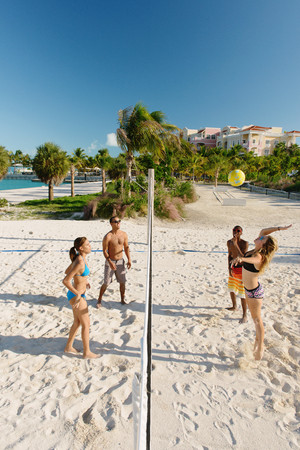 Four young adult friends playing beach volleyball, Providenciales, Turks and Caicos Islands, Caribbean