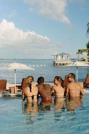 Four young adults chatting in swimming pool, Providenciales, Turks and Caicos Islands, Caribbean