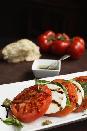 Sliced vine tomatoes and mozzarella with basil and dressing LANG_EVOIMAGES
