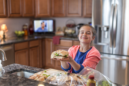 oversized: Girl in kitchen preparing sandwich LANG_EVOIMAGES