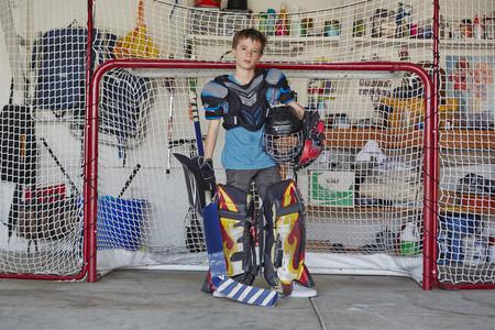 protects: Boy in hockey goal wearing protective sportswear