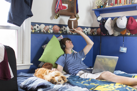 pooches: Teenage boy lying on bed with laptop computer, football and dog