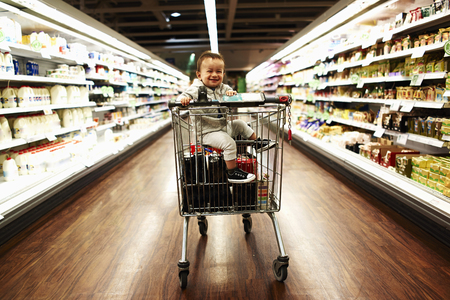 Baby boy sitting in supermarket trolley LANG_EVOIMAGES