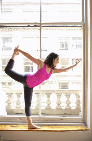 limber: Woman doing dancer pose by window