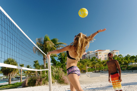 Young adult friends playing beach volleyball, Providenciales, Turks and Caicos Islands, Caribbean