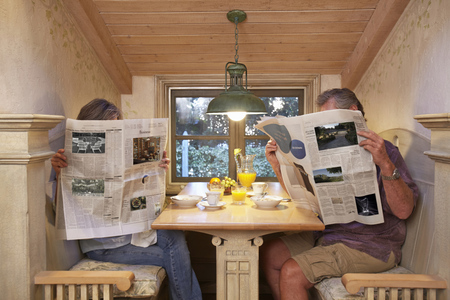 Couple at breakfast table, ignoring each other, reading newspapers