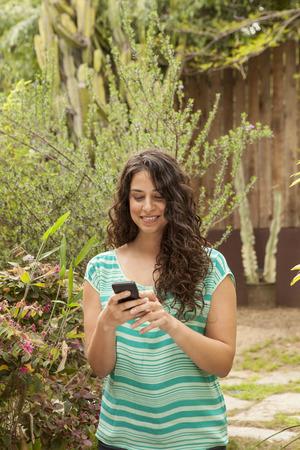 Girl in garden using smartphone