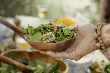 detoxing: Close up of hand holding salad bowl at garden party LANG_EVOIMAGES