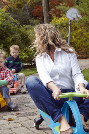 woman hanging toy: Mother and young sons riding on toy cars in garden
