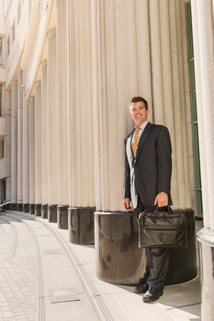 negative area: Portrait of business lawyer with briefcase outside courthouse