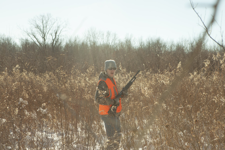 winter escape: Teenage boy hunting with shotgun in Petersburg State Game Area, Michigan, USA