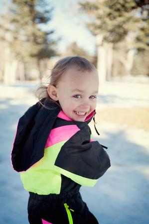 Girl in snow, looking over shoulder