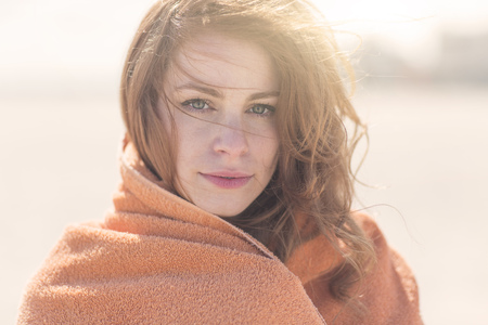 Close up portrait of young woman wrapped in blanket