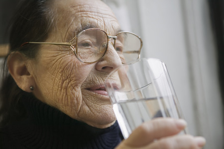Senior woman with glass of drinking water