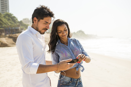 decide deciding: Couple choosing music from smartphone, Arpoador beach, Rio De Janeiro, Brazil LANG_EVOIMAGES