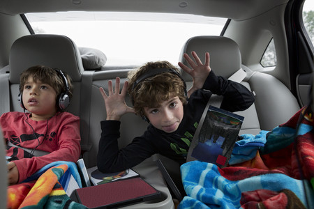 6 7 year old: Brothers in back seat of car, wearing headphones LANG_EVOIMAGES