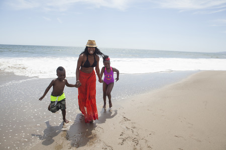 Mother and children walking on beach LANG_EVOIMAGES