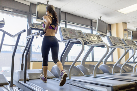 low self esteem: Mid adult woman running on treadmill in gym