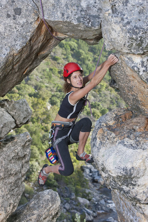 treading: Young female rock climber climbing up rock face LANG_EVOIMAGES